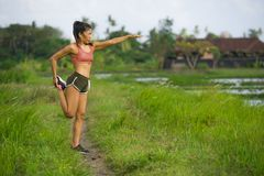 Mulher asiática do corredor apto e desportivo que esticam o pé e corpo após ter corrido o exercício no fundo bonito do campo verd fotos de stock