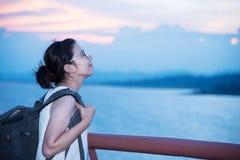 Mulher asiática do mochileiro que respira o ar fresco no mar e no céu do por do sol imagens de stock