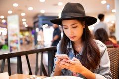 Mulher asiática do moderno novo que veste um chapéu negro usando seu smartpho fotografia de stock royalty free