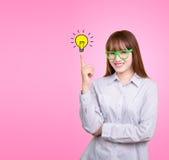 A mulher asiática do negócio com vidros verdes está e tem a lâmpada da ideia Imagens de Stock Royalty Free