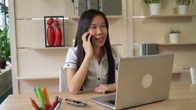 Mulher asiática do retrato no escritório que fala com cliente filme