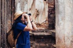 Mulher asiática do turista que toma a foto de antigo do archi tailandês do templo imagens de stock