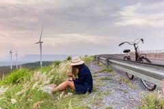 Mulher asiática do viajante no feriado de relaxamento do vestido de brim com bicicleta clássica foto de stock