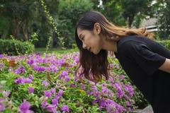 Mulher asiática dobrada para baixo para olhar a buganvília roxa das flores com fundo do parque público fotos de stock royalty free