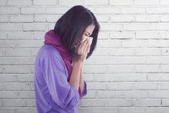 Mulher asiática doente com a gripe e a febre que guardam o tecido no nariz Imagens de Stock Royalty Free