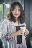 Mulher asiática e copo de café quente à disposição que relaxam o sorriso da emoção foto de stock
