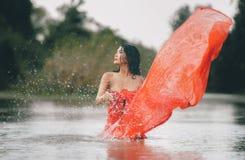 Mulher asiática em um roupão vermelho e para apreciar a natureza no selvagem fotos de stock royalty free