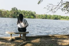Mulher asiática em uma cadeira que senta-se apenas no rio , Fundo da ponte e do lago Foto de Stock Royalty Free