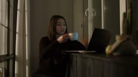 Mulher asiática encantador que trabalha com o portátil na noite video estoque