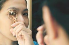 A mulher asiática está usando o encrespador da pestana Fotografia de Stock