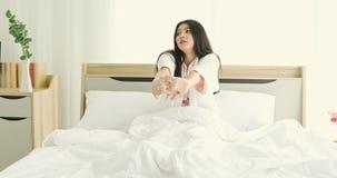 A mulher asiática estica para fora na cama