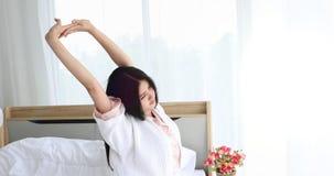A mulher asiática estica para fora na cama no quarto