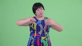 Mulher asiática excesso de peso nova confusa que escolhe entre os polegares acima e os polegares para baixo filme