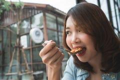 Mulher asiática feliz bonita que come uma placa dos espaguetes italianos do marisco no restaurante imagem de stock