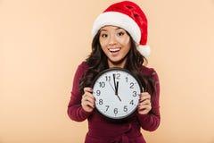 Mulher asiática feliz no chapéu vermelho de Santa Claus que guarda o pulso de disparo que mostra n Fotos de Stock