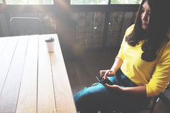 Mulher asiática feliz que conversa em seu telefone celular ao relaxar no café durante o tempo livre, fotos de stock royalty free