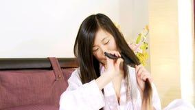 Mulher asiática feliz que escova o cabelo longo em casa video estoque