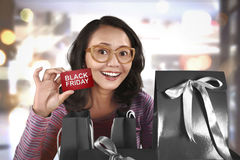 Mulher asiática feliz que guarda o cartão com Black Friday Fotos de Stock