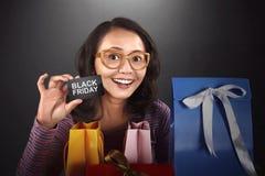 Mulher asiática feliz que guarda o cartão com texto de Black Friday Imagem de Stock