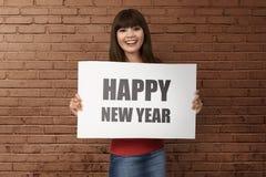 Mulher asiática feliz que guarda o cumprimento do ` s do ano novo feliz Fotografia de Stock