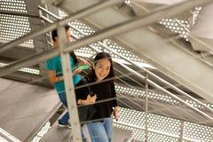 Mulher asiática feliz que sorri ao andar abaixo das escadas com seu amigo fotos de stock royalty free