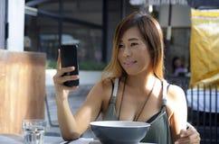 Mulher asiática feliz que usa o telefone celular que toma o phot do retrato do selfie imagem de stock