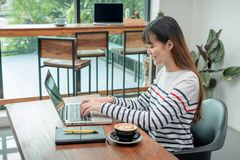 Mulher asiática feliz que usa-se no laptop ao trabalhar perto dos wi Imagem de Stock