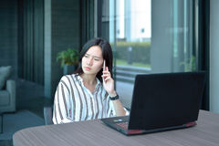 Mulher asiática forçada do negócio ocasional que telefona e que pensa dentro para Fotos de Stock Royalty Free
