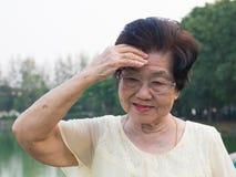 A mulher asiática idosa vestiu uns vidros não era confortável com dores de cabeça Quando mulher superior que anda no parque imagem de stock