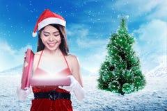 Mulher asiática na caixa de presente da abertura do traje de Papai Noel foto de stock