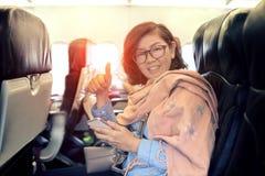 Mulher asiática no assento da classe de economia do sinal doméstico do plano da linha aérea fotos de stock royalty free
