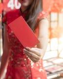 Mulher asiática no cheongsam tradicional do vestido chinês que guarda p vermelho imagem de stock