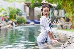 Mulher asiática no curso de relaxamento das férias da piscina do hotel, moça que aprecia termas imagens de stock