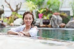 Mulher asiática no curso de relaxamento das férias da piscina do hotel, moça que aprecia termas fotos de stock
