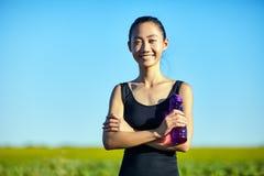 Mulher asiática no sportswear com a garrafa de água que está no campo imagens de stock