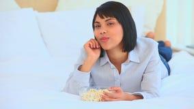 Mulher asiática no telefone que come a pipoca filme