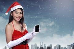 Mulher asiática no traje de Papai Noel que guarda o telefone celular Foto de Stock