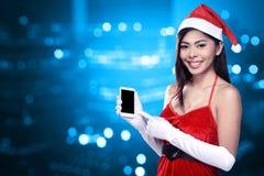 Mulher asiática no traje de Papai Noel que guarda o telefone celular Imagens de Stock Royalty Free