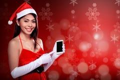 Mulher asiática no traje de Papai Noel que guarda o telefone celular Foto de Stock Royalty Free