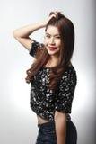 A mulher asiática no vestido preto da lantejoula escova sua parte traseira do cabelo Imagens de Stock Royalty Free