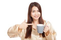 A mulher asiática nos pijamas aponta à escova de dentes na caneca Foto de Stock