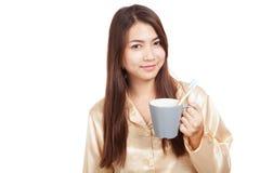 Mulher asiática nos pijamas com a escova de dentes na caneca Imagens de Stock Royalty Free