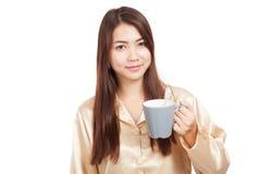 Mulher asiática nos pijamas com a escova de dentes na caneca Fotografia de Stock Royalty Free