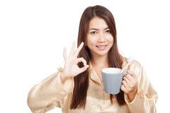 A mulher asiática nos pijamas mostra ESTÁ BEM com a escova de dentes na caneca Imagem de Stock Royalty Free