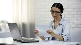 Mulher asiática nos vidros que lê a letra, intimação, recibo da correspondência imagens de stock royalty free