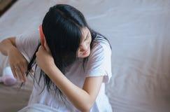 Mulher asiática nova após o banho que hairbrushing seu cabelo com pente foto de stock