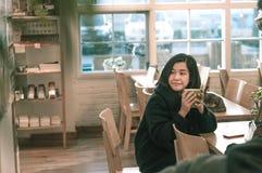 A mulher asiática nova aprecia com bebidas e o café fotografia de stock royalty free