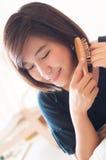 A mulher asiática nova aprecia pentear seu cabelo imagens de stock royalty free