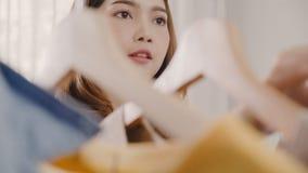Mulher asiática nova atrativa bonita que escolhe sua roupa do equipamento da forma no armário em casa ou na loja A menina pensa o fotos de stock royalty free
