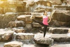 A mulher asiática nova bonita é ioga do exercício do exercício no parque foto de stock